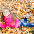 Autumn portrait of cute little girl lying in maple leaves — Stock Photo