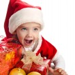 Happy little girl with gift christmas boxes balls and hat — Stock Photo