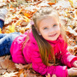 Autumn portrait of cute little girl lying in maple leaves — Stock Photo #33324059