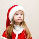 Cute little girl in christmas hat dreaming and looking up — Stock Photo
