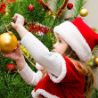 Little girl in santa hat decorating the christmas tree  — Stockfoto