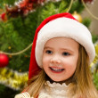 Cute little girl in santa hat near the christmas tree — Zdjęcie stockowe
