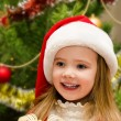 Cute little girl in santa hat near the christmas tree — Stok fotoğraf