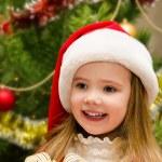 Cute little girl in santa hat near the christmas tree — Stock Photo