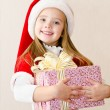 Happy smiling little girl with christmas present — Stock Photo