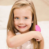 Portrait of smiling little girl brushing her hair — Stock Photo