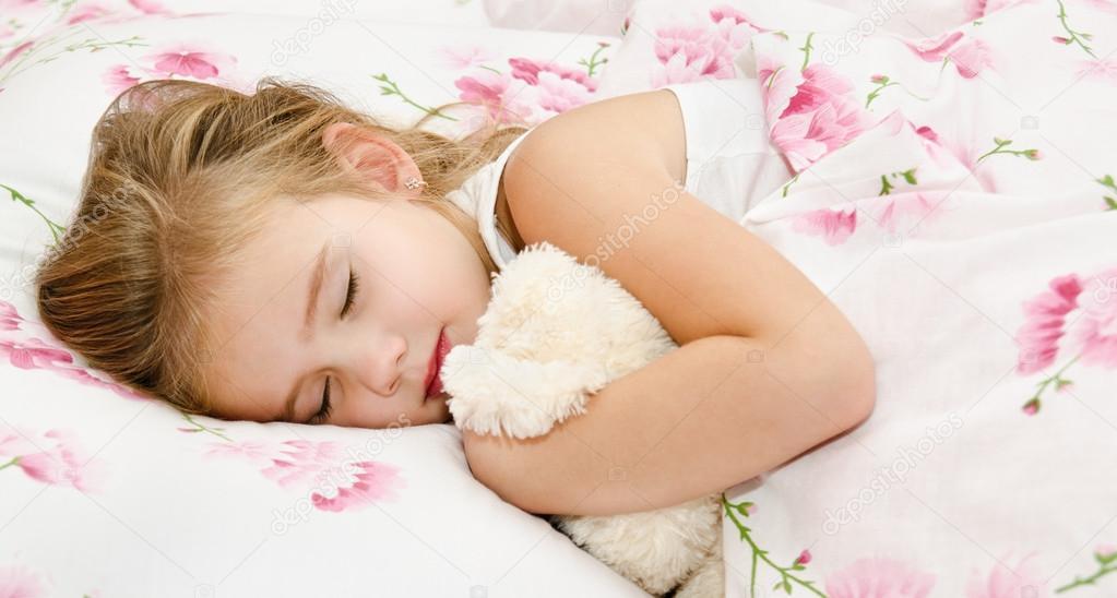 Чарівної маленької дівчинкою спати в ліжку зі своєю іграшкою.