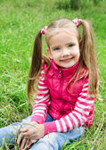 Cute smiling little girl lying in grass on the meadow — Stock Photo