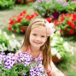 Outdoor portrait of cute little girl near the flowers  — Stock Photo
