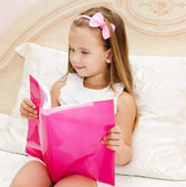 Cute little girl reading a book — Stockfoto