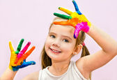 Cute smiling little girl with hands in paint — Stock Photo
