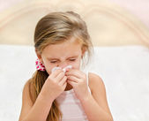 Little girl blowing her nose in a great effort — Stock Photo