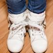Pair of white leather shoes with laces tied together on girl's l — Stock Photo