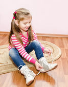 Cute little girl tying her white shoes — Stock Photo