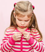 Cute little girl buttoning her jacket — Stock Photo