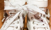 Pair of white leather girls shoes with laces tied together — Stock Photo