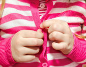 Little girl buttoning her jacket — Stock Photo