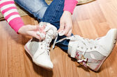 Little girl tying her white shoes at home — Stock Photo