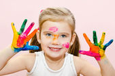 Cute smiling little girl with hands in paint — Stockfoto