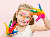 Cute smiling little girl with hands in paint — Photo