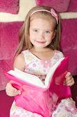 可爱微笑的小女孩读一本书 — 图库照片
