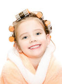 Portrait of smiling cute little girl in hair curlers and bathrob — Stockfoto