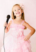 Beautiful little girl with microphone in princess dress — Stock Photo