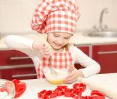 Leende liten flicka med kock hat stirrring cookie deg — Stockfoto