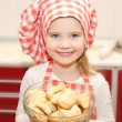 Stock Photo: Smiling little girl in chef hat holding bowl with cookies