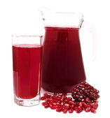 Pomegranate juice in pitcher and pomegranates isolated on white — Stock Photo
