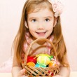 Little girl with basket full of colorful easter eggs — Stock Photo