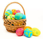 Colorful easter eggs in the basket isolated on a white — Stock Photo