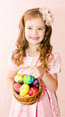 Cute smiling little girl with basket full of colorful easter egg — Stock Photo