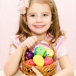 Stock Photo: Cute little girl with basket full of colorful easter eggs