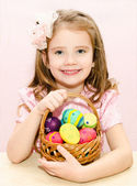 Cute little girl with basket full of colorful easter eggs  — Stock Photo