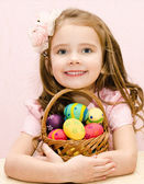 Cute smiling little girl with basket full of easter eggs  — Stock Photo