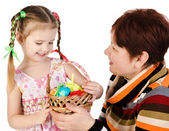 Little girl and her grandmother with basket full of easter eggs  — Stock Photo