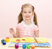 Cute smiling little girl drawing with paint and paintbrush — Stock Photo