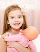 Adorable little girl playing with a doll  — Stock Photo
