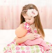 Linda niña sonriente jugando con una muñeca — Foto de Stock
