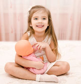 Cute smiling little girl playing with a doll — Stock Photo