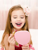 Little girl with lipstick and  mirror  — Stock Photo