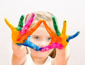 Cute little girl with hands in paint — Stock fotografie