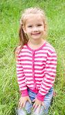 Portrait of adorable smiling little girl sitting on grass — Stock fotografie
