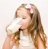 Beautiful little girl drinking milk — Stock Photo