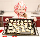 Smiling little girl in chef hat with baking sheet of cookies — Стоковое фото