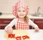 Little girl cuts dough with form for cookies  — Стоковое фото