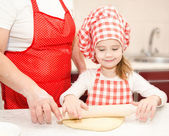 Little girl and grandmother rolling dough for cookies — Стоковое фото