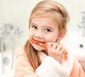 Cute little girl brushing teeth in bath  — Stock Photo