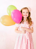 Cute smiling little girl with balloons — Stock Photo